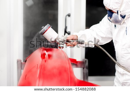 Automotive industry - engineer working on painting a red car in special booth