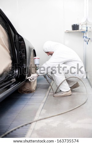 Automotive mechanical engineer painting the body of a black car  - stock photo