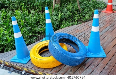 Automotive Safety Concepts, Two Painted Tires with Blue and White Traffic Cones. - stock photo