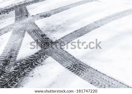 Automotive tire tracks on fresh wet snow - stock photo