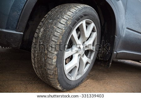 Automotive wheel with light alloy disc on dirty country road, closeup photo