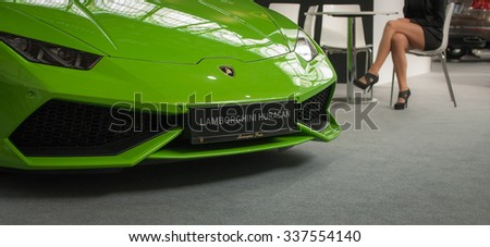 AUTOSHOW PRAHA, PRAGUE, CZECH REPUBLIC - October 4, 2015: Shiny bright lime green Lamborghini Huracan car front  mask, logo and legs of a guarding supermodel