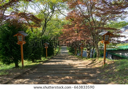 Autumn alley in park with red trees and decorative lights, Japanese park in fall season