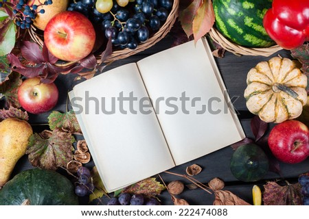Autumn and Thanksgiving concept. Seasonal fruit and pumpkins in basket on wood background with open old book to place your text. - stock photo