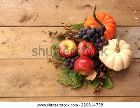 Autumn and Thanksgiving concept. Seasonal fruit and pumpkins on wood background. - stock photo