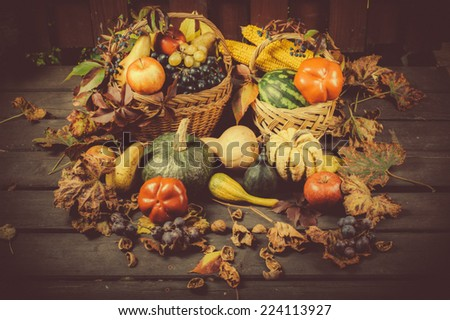 Autumn and Thanksgiving concept. Seasonal fruit and pumpkins on wood background.