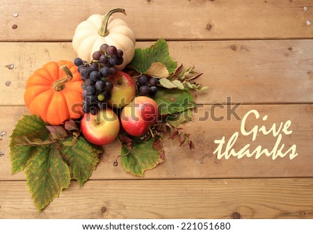 "Autumn and Thanksgiving concept. Seasonal fruit and pumpkins on wood background with the phrase ""Give thanks"" on the right. - stock photo"