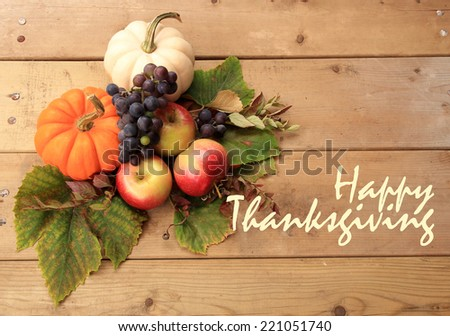 "Autumn and Thanksgiving concept. Seasonal fruit and pumpkins on wood background with the phrase ""Happy Thanksgiving"" on the right. - stock photo"