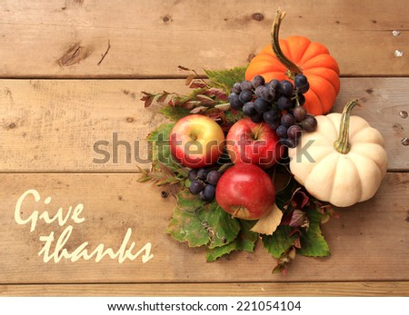 "Autumn and Thanksgiving concept. Seasonal fruit and pumpkins on wood background with the phrase ""Give thanks"" on the left. - stock photo"