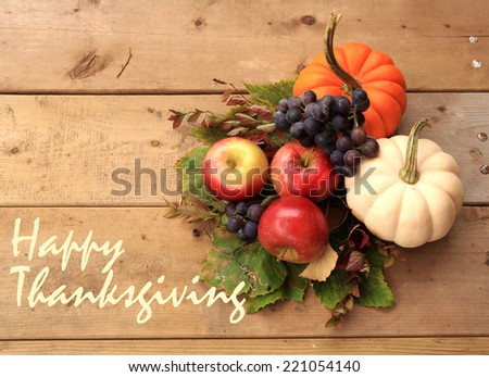 "Autumn and Thanksgiving concept. Seasonal fruit and pumpkins on wood background with the phrase ""Happy Thanksgiving"" on the left. - stock photo"