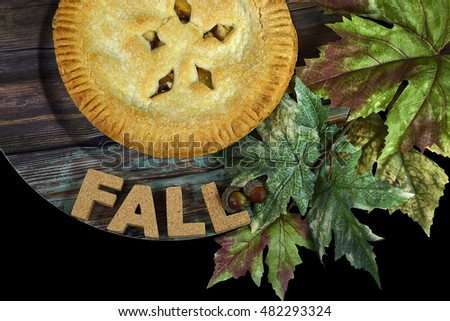 autumn apple pie with leaves and cork letters on wood plate
