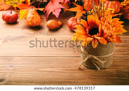 Autumn arrangement - pot with artificial granat, sunflower, cones and leaves on wooden background.