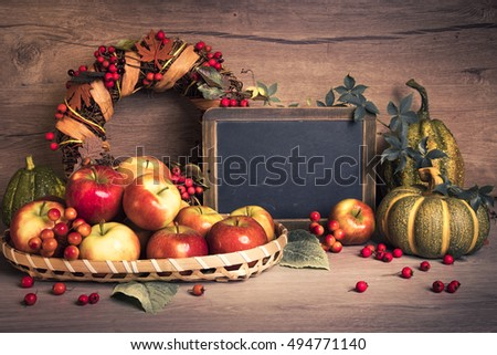 Autumn arrangement with apples, decorations and text space on the chalk board. This image is toned.