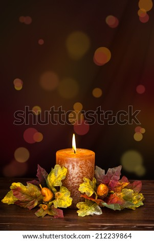 Autumn arrangement with candle against de-focused holiday lights. - stock photo