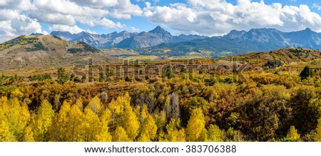 Autumn at Sneffels Range - Panoramic fall view of rugged Sneffels Range, northwest edge of San Juan Mountains of Colorado Rockies. Mt. Sneffels, 14,158-ft (4,315m), is the highest peak in the middle. - stock photo