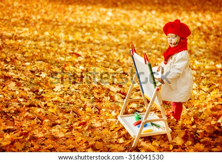 Autumn Baby Artist Painting Fall Yellow Leaves, Creative Kid Girl Drawing Inspiration - stock photo
