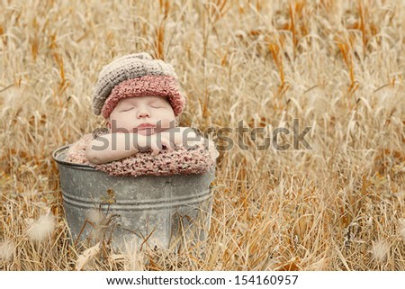 Autumn baby sleeping in a bucket for a portrait.