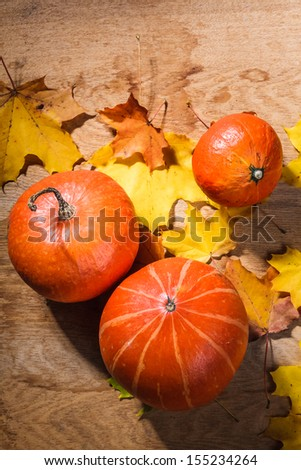 Autumn background with colored leaves and pumpkin on wooden board. Pumpkins on grunge wooden backdrop, background table. Autumn, halloween, pumpkin - stock photo