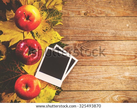 Autumn background with colorful leaves and apples on rustic wooden board. Creating fall season memories with retro photo cards of photo frames. Thanksgiving and Halloween holidays concept. Copyspace - stock photo