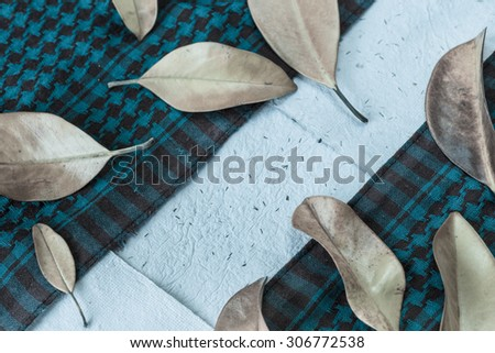 Autumn background with colorful yellow orange leaves of magnolia on blue checkered fabric and hand-made paper background. Fall theme, Autumn concept background with yellow fall leaves and copy space - stock photo