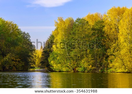 Autumn Background with Colourful Trees near the River and Cloudy Blue Sky at Sunny Day