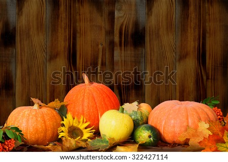 Autumn background with maple leaves and pumpkins on wooden table - stock photo