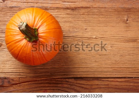 autumn background with pumpkin on wooden board  - stock photo