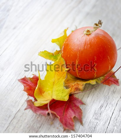 Autumn background with pumpkins and autumn leaves on wooden table/Thanksgiving day concept - stock photo