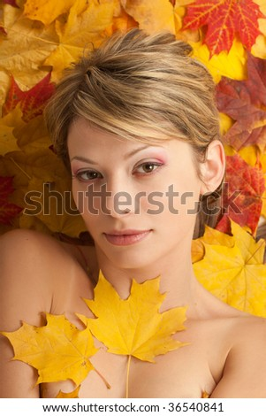 Portrait of attractive nudity woman covering by maple leafs stock image