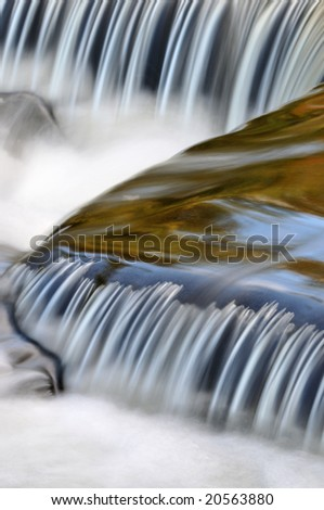 Autumn, Bond Falls cascade illuminated with reflected color from sunlit foliage and blue sky overhead, Michigan's Upper Peninsula, USA - stock photo