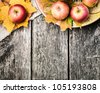 Autumn border from apples and fallen leaves on old wooden table. Thanksgiving day concept - stock photo