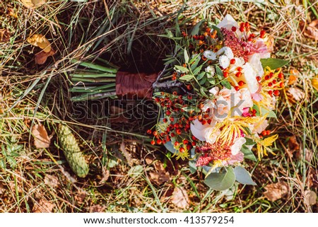 Autumn bouquet of yellow and orange flowers, red berries and maple leaves lying on the grass