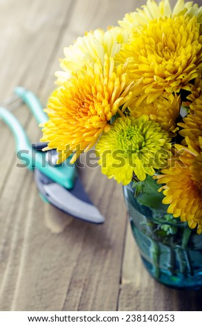Autumn bouquet of yellow chrysanthemums in a vase on a wooden background