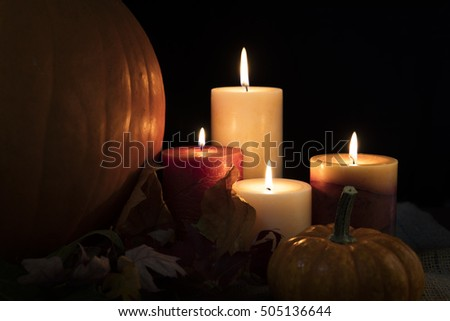 Autumn candles burning surrounded by leaves and gourds.