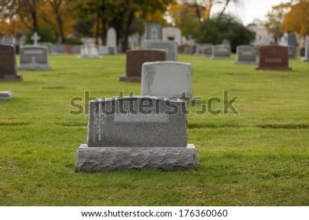 Autumn cemetery grave stone tombstone - stock photo