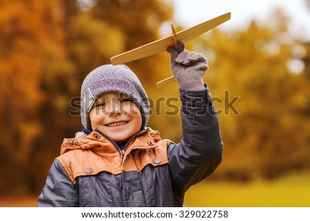 autumn, childhood, dream, leisure and people concept - happy little boy playing with wooden toy plane outdoors - stock photo
