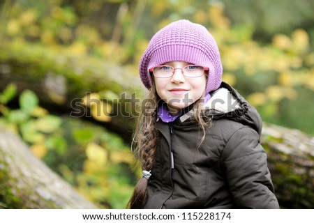Autumn close-up portrait of little girl in glasses wearing pink hat - stock photo