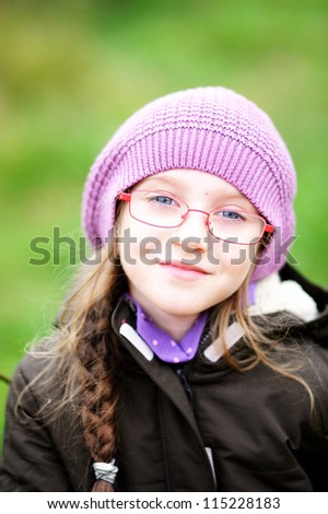 Autumn close-up portrait of little girl in glasses wearing pink hat
