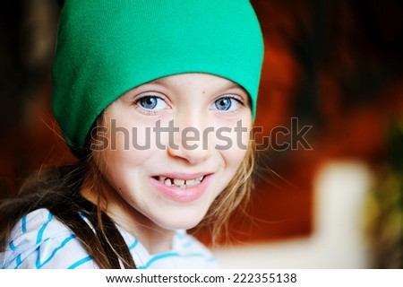 Autumn close-up portrait of little girl  wearing green  hat - stock photo