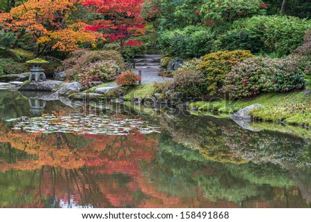 Autumn Color Reflections in Pond in Japanese Garden. Buddhist Stone Lantern. Copy space. - stock photo