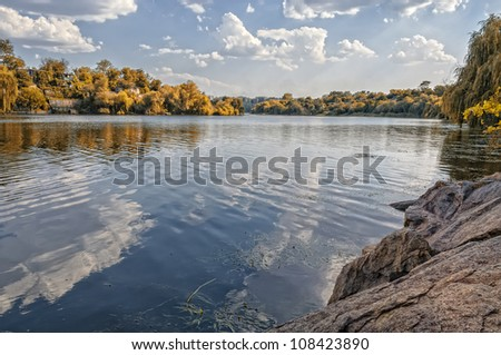 Autumn colorful foliage over lake with beautiful woods - stock photo