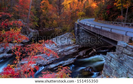 Autumn colors, bridge over water with red colors  - stock photo
