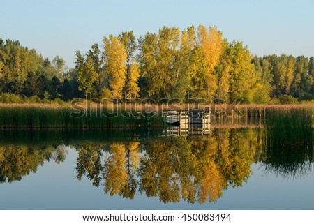 Autumn Colors Reflected on a Lake with a Fishing Dock - stock photo