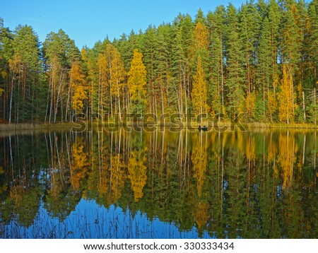 autumn colors reflected on the water of a finnish lake - stock photo