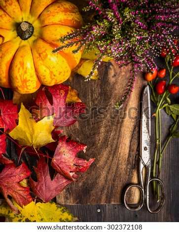 Autumn composing with foliage, pumpkin and vintage scissors on rustic wooden background, top view - stock photo