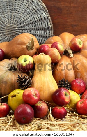 Autumn composition of fruits and pumpkins on straw on wooden background