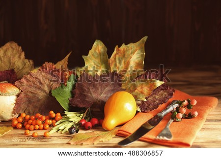 Autumn composition of leaves, berries, vegetables, knife and fork on wooden table. Thanksgiving day concept