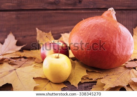 Autumn composition with pumpkin, yellow maple leaves and apple on rustic wooden table. Thanksgiving holiday and harvest concept.Selective focus. - stock photo