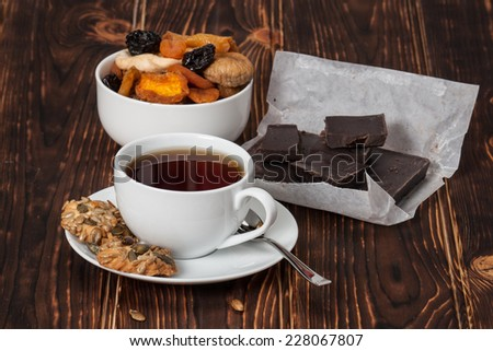 Autumn Concept. Cup Of Tea Or Coffee. Dried Fruits. Dark Chocolate. Wooden Background.