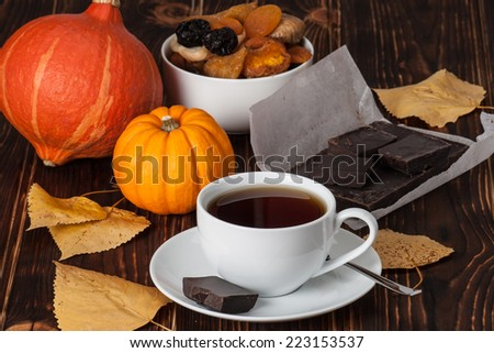 Autumn Concept. Cup Of Tea Or Coffee. Dried Fruits. Pumpkins. Dark Chocolate. Wooden Background.